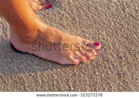 Young woman standing alone on the beach in the sunset close - stock photo