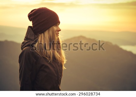 Young Woman standing alone outdoor with sunset mountains on background Travel Lifestyle and survival concept rear view - stock photo