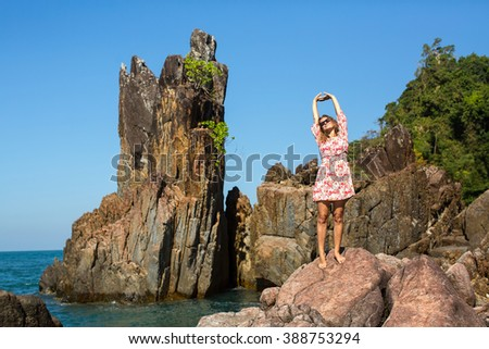 Young woman standing among the coastal cliffs.