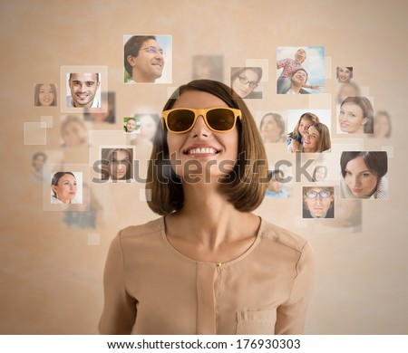 Young woman standing and smiling with many different people's faces around her. Technology social media network of friends and communication.