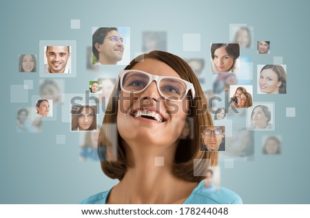 Young woman standing and smiling with many different people's faces around her. Technology social media network of friends and communication. - stock photo