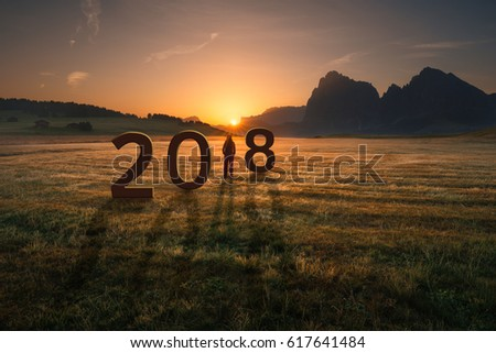 Young woman standing and watching the rising sun, uncertainty for 2018 new year. Future and time passing concept.