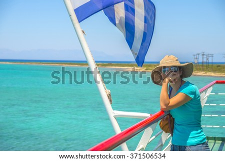 Young woman  standing at a yacht on a sunny day and looking at the sea. Summer in Greece.