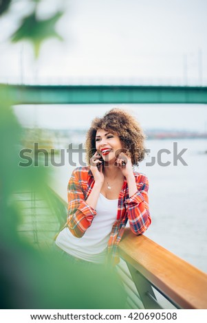 Young woman standing at the balcony and talking on mobile phone