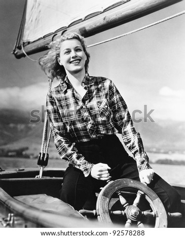 Young woman standing at the helm of a sailboat and holding the wheel - stock photo