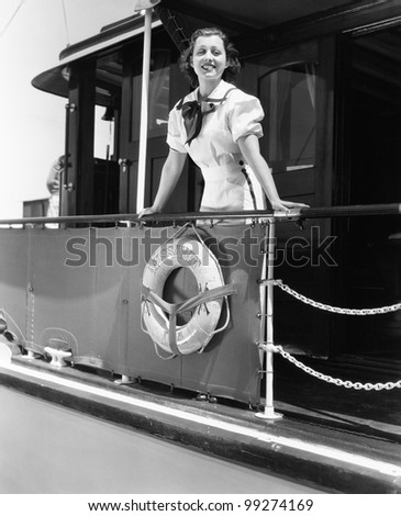 Young woman standing at the railing of a boat and smiling