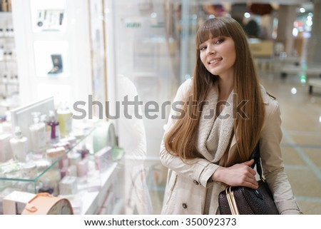 Young woman standing at the showcase in mall