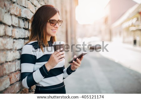 Young woman standing at the street drinking coffee to go and using mobile phone  - stock photo