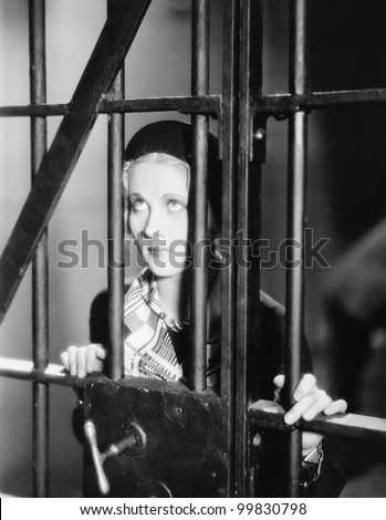 Young woman standing behind bars in a prison cell
