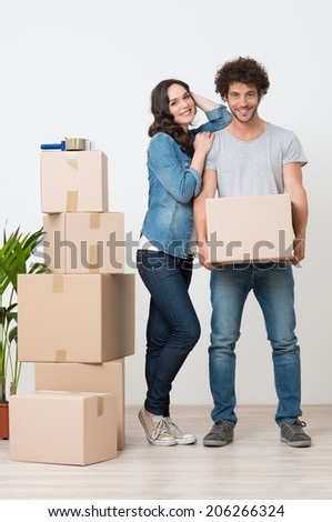 Young Woman Standing Besides Man Holding Cardboard Box - stock photo