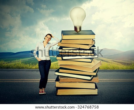 Young woman standing by pile of old books with bright light bulb on top of it on countryside road  - stock photo