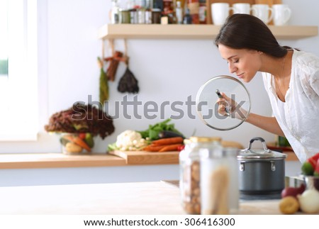 Young woman standing by the stove in the kitchen . - stock photo