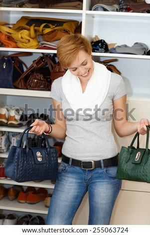 Young woman standing front of open wardrobe, hesitating which bag to take. - stock photo