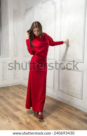 Young woman standing in a long red dress, watching down - stock photo