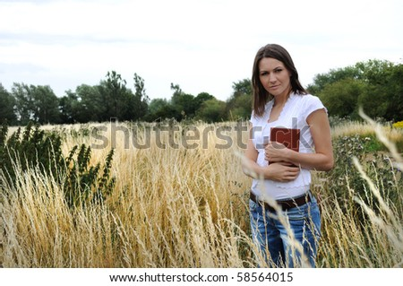 Young woman standing  in field with book - stock photo