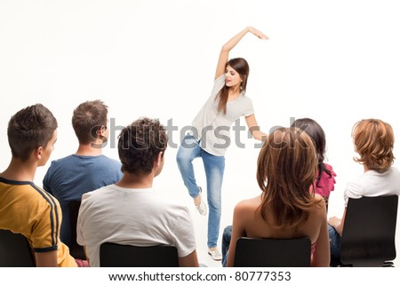 young woman standing in front of crowd gesturing