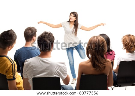 young woman standing in front of crowd gesturing - stock photo