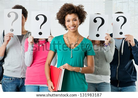 Young Woman Standing In Front Of Friends Holding Paper With Question Marks