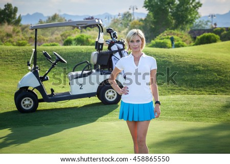 Young woman standing in front of golf cart on golf course with bright blonde hair headshot portrait