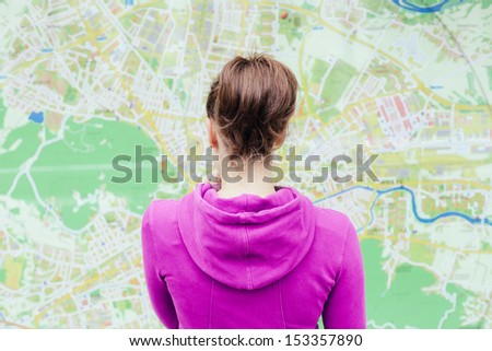 Young woman standing in front of tourist city map - stock photo