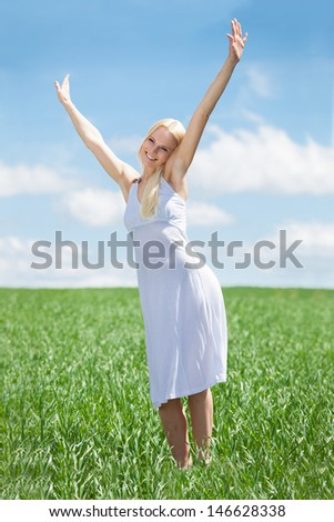 Young Woman Standing In Grass With Arm Raised - stock photo