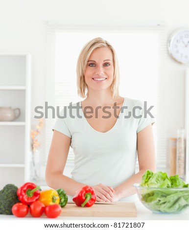 Young woman standing in kitchen smiling into camera