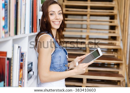 Young woman standing in office with notepad