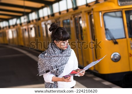 Young woman standing in public tramway or train station with the map of the city in Berlin. Yellow train in the background. Color toned image. Selective focus. - stock photo