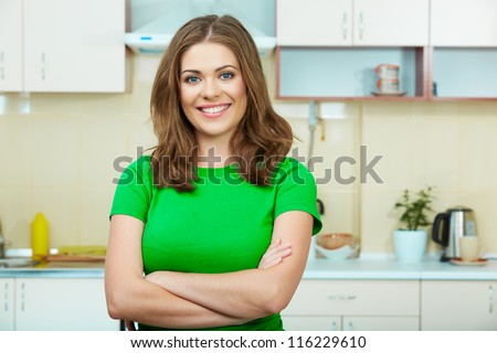 Young woman  standing in the house kitchen. Clothes of green color. - stock photo