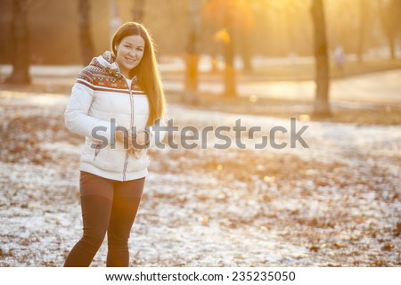 Young woman standing in the park in sunlight of sunset sun, copyspace - stock photo
