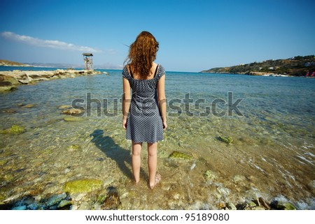 Young woman standing in water not far from the coastline - stock photo