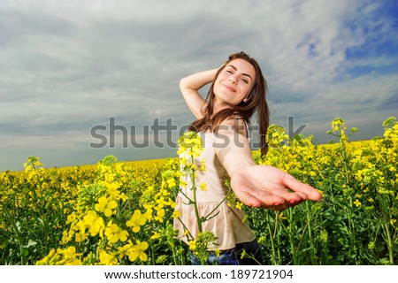 Young woman standing in yellow rapeseed field smiling at camera. With one hand in her hair and one hand reaching to the camera. Blue sky background!  - stock photo