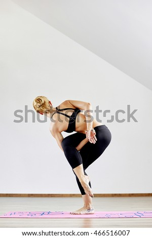 Young woman standing in yoga pose on rubber mat