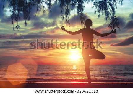 Young woman standing in yoga pose on the beach during the amazing sunset. - stock photo