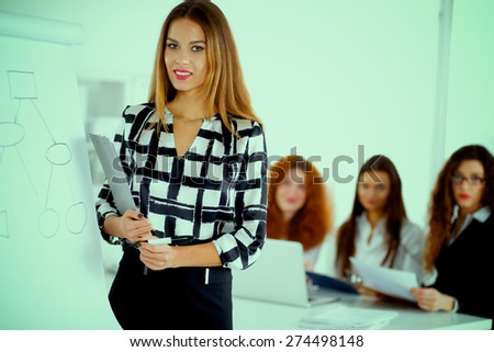 Young woman standing near board with folder - stock photo