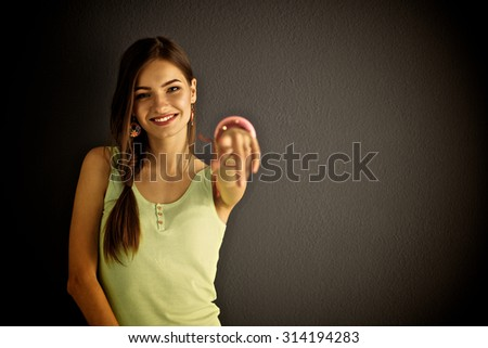 Young woman standing near dark wall pointing you