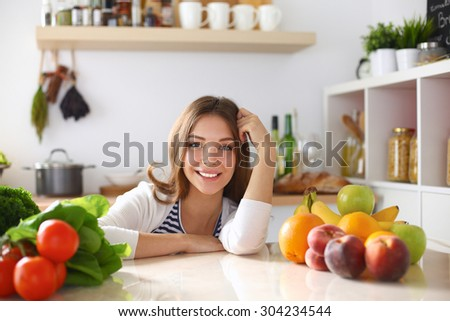 Young woman standing near desk in the kitchen .