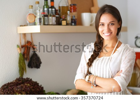 Young woman standing near desk in the kitchen - stock photo
