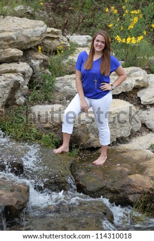Young woman standing near rushing water attraction at Stephen's Lake Park in Columbia, Missouri