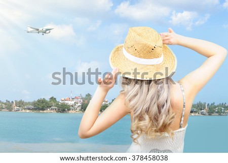 Young woman standing near sea and holding a hat - stock photo
