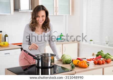 Young Woman Standing Near The Induction Cooker Cooking Meal In Kitchen - stock photo