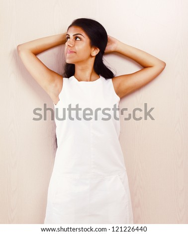 Young woman standing near wall background.