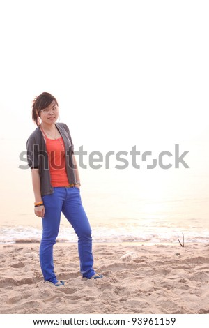Young woman standing on a beach - stock photo