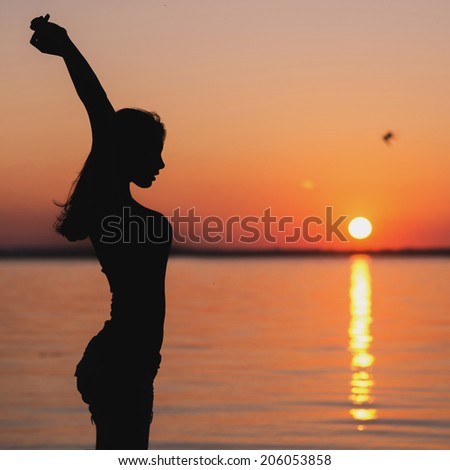Young woman standing on a beach and doing yoga exercises - stock photo