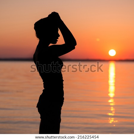 Young woman standing on a beach and doing yoga exercises outdoor - stock photo