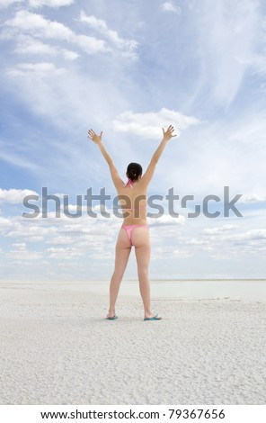 Young woman standing on a beach and enjoying the sun - stock photo