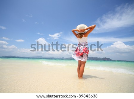 Young woman standing on a beach and looking to a sea - stock photo