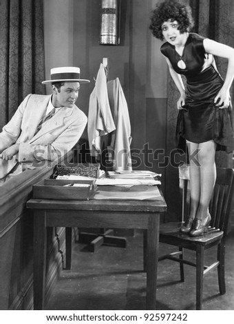 Young woman standing on a chair with a young man looking at her legs