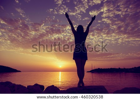 Young woman standing on a rocky shore of Syvota bay, Greece, looking at sunset and enjoying beauty and freedom - stock photo