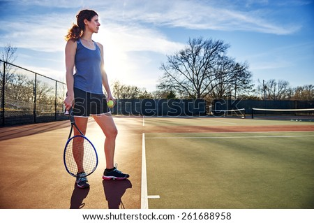young woman standing on a tennis court - stock photo